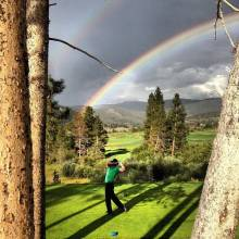 Mountain golfing under a rainbow